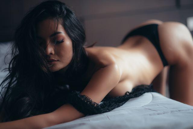 sexy Frau beugt sich vor aufs Bett