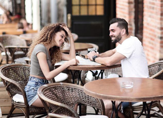 Paar sitzt zusammen im Straßencafé