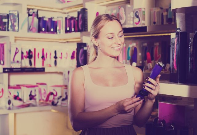 Woman choosing toys in a sex shop
