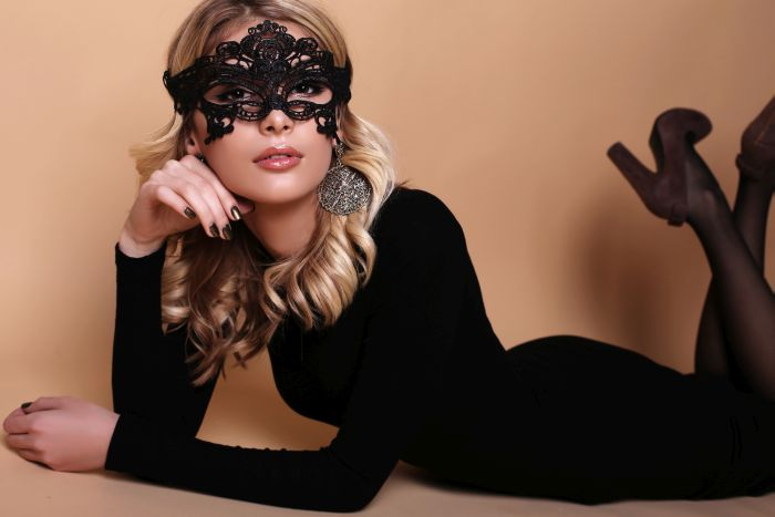 woman with lacy mask laying down