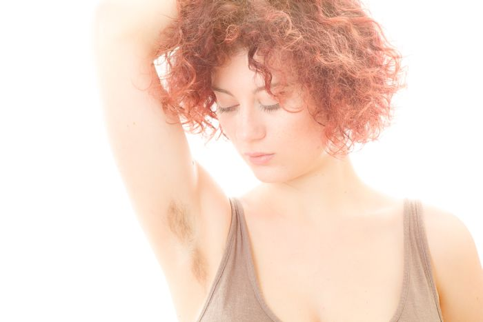 Attractive red haired woman with a little armpit hair