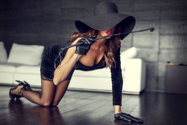 Sexy woman with hat and whip