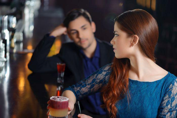 Woman and man making eye contact at a bar