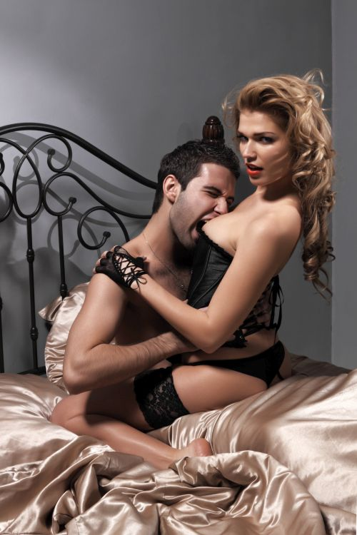 man biting in the breast of a hot blonde woman