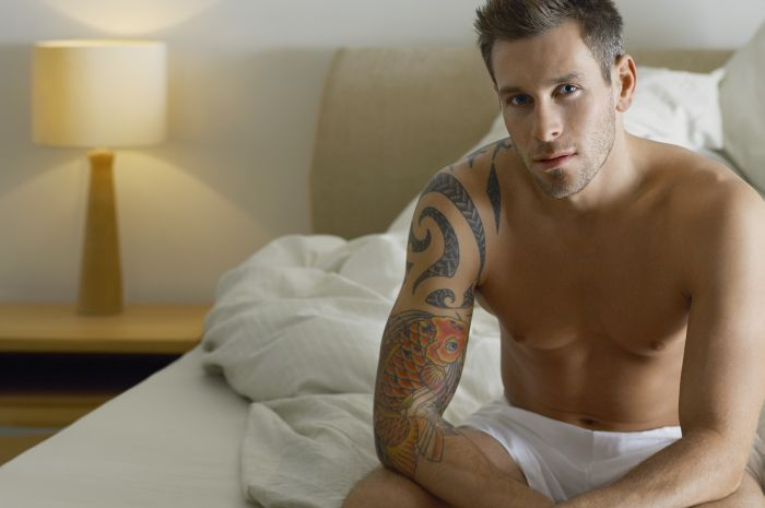 sexy half naked man with a tattoo in bed