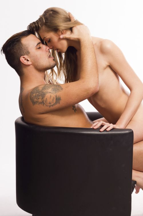 naked couple kissing on a black chair