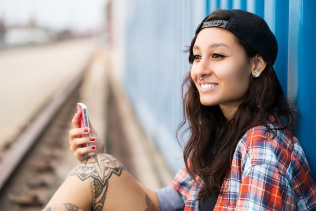 Smiling tattooed ciswoman with smartphone
