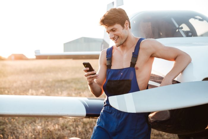 barely dressed man with a phone next to a plane