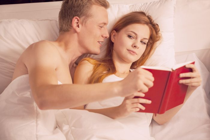 couple reading book in bed to get erotic ideas