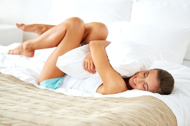 Sexy blonde in bed with period cramps