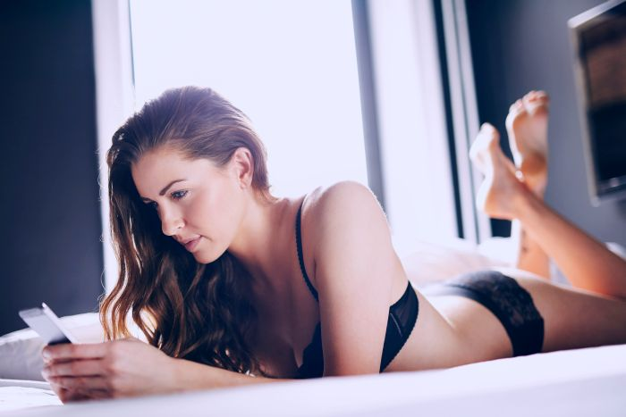 Attractive lady texting on the bed