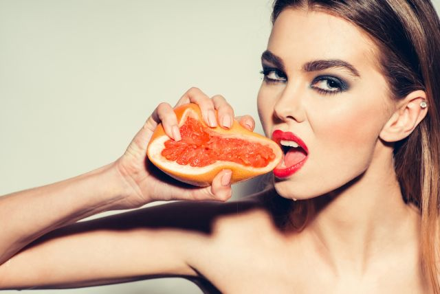 Sexy woman about to give a grapefruit blow job