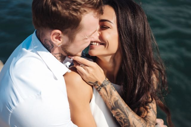 Young tattooed couple kissing by the sea
