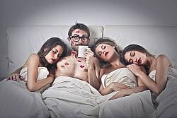 Three beautiful girls with a guy on bed