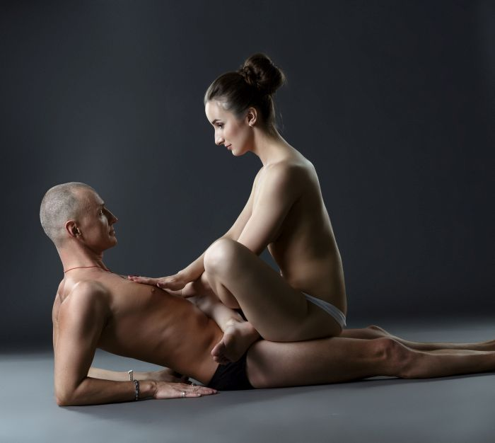 Naked woman on top of man in lotus position