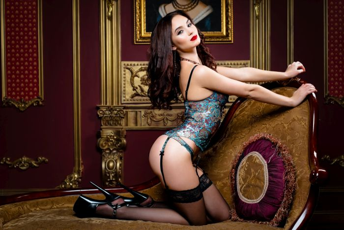 Hot and sensuous brunette with long curly hair in high heels and eye-catching lingerie