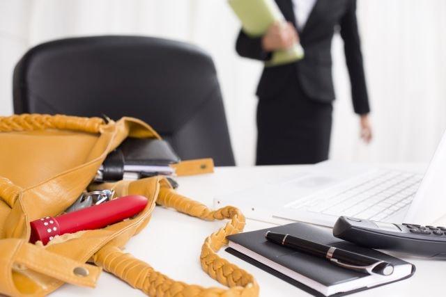 open handbag with vibrator on office desk