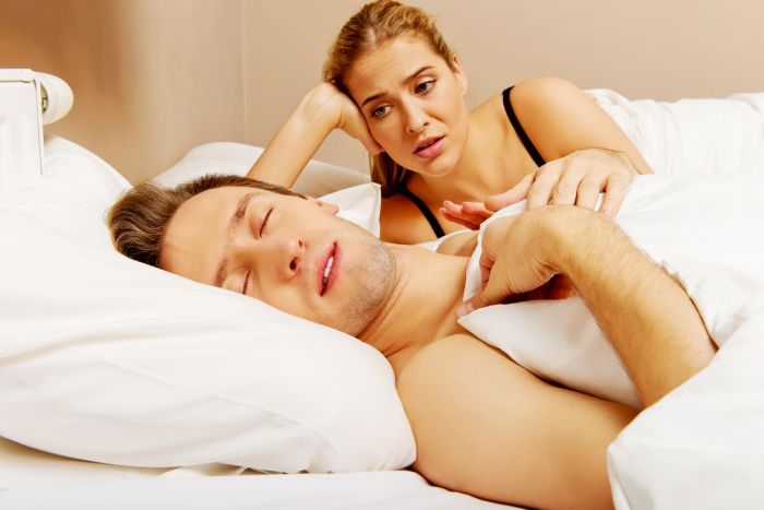 Man sleeping in bed with blonde partner looking annoyed