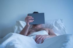 Man in bed watching porn on his tablet