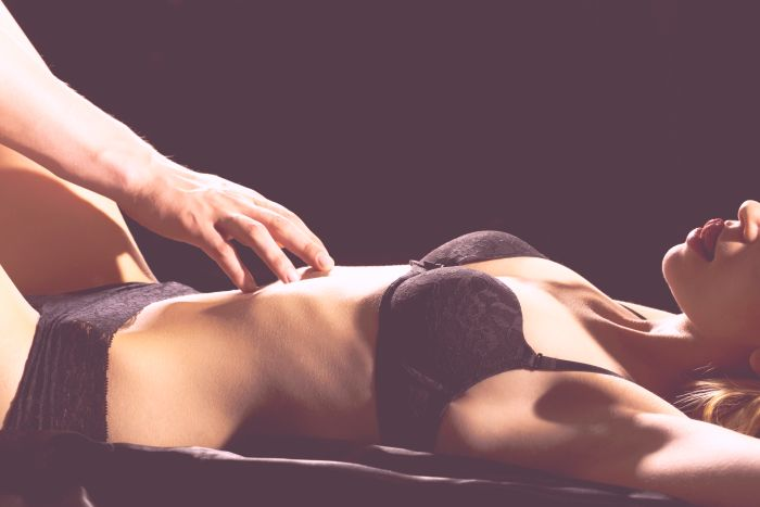 Woman's body lying being touched by a male hand
