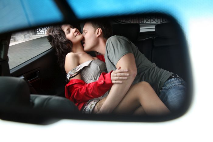 couple kissing heavily in the car
