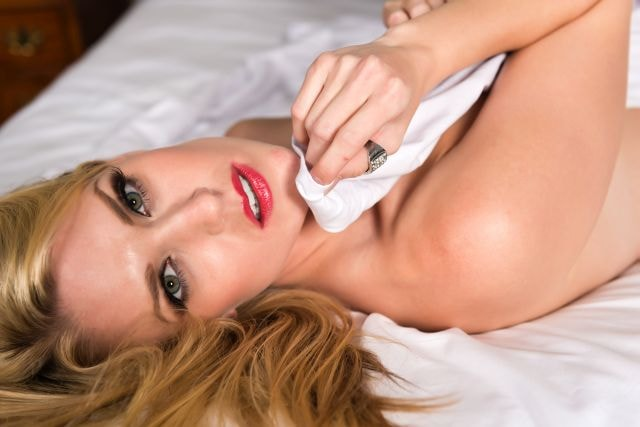 Sexig blond kvinna som ligger på sängen