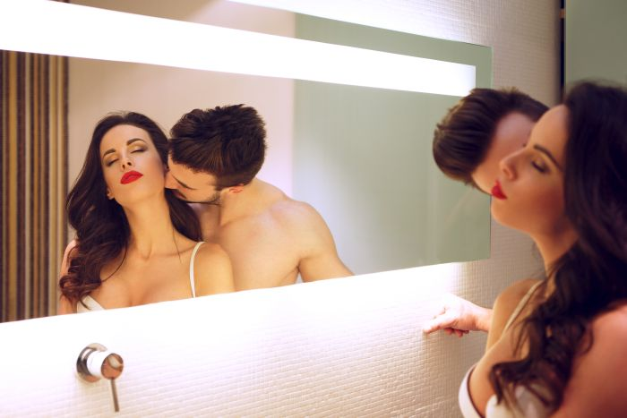 couple making out in front of a mirror