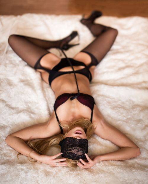 hot mature woman lying on the bed with lace eye cover and whip