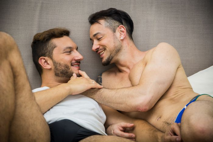 Men couple laying on the bed being intimate