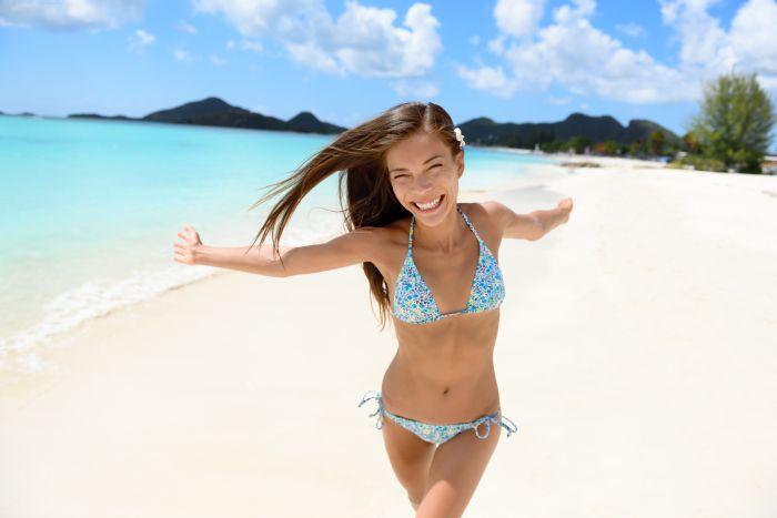 Cute Asian girl in blue bikini on beach