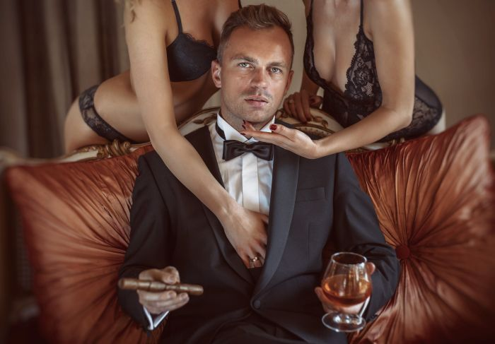 rich man with a drink and two girls in his hands