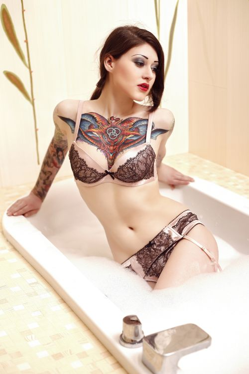 beautiful tattooed girl in a hot bath