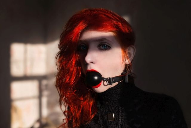 Sexy red-haired woman wearing a ball gag