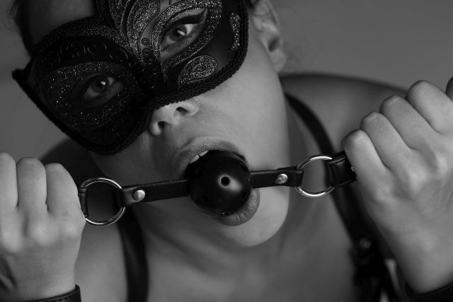 Woman wearing a mask and a ball gag