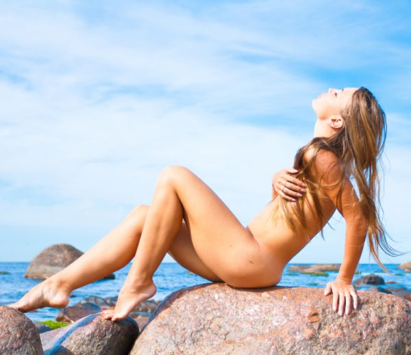 Naked woman on a rock by the ocean