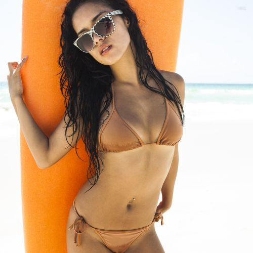 Sexy Asian girl posing with her surfboard