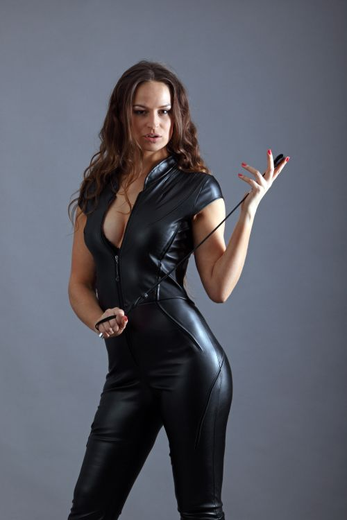 dominant brunette in leather holding a whip