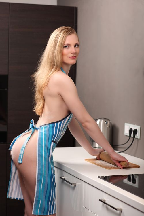 sexy naked wife wearing a pinafore in the kitchen