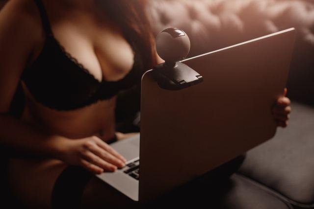 Frau in Reizwäsche sitzt vor Webcam