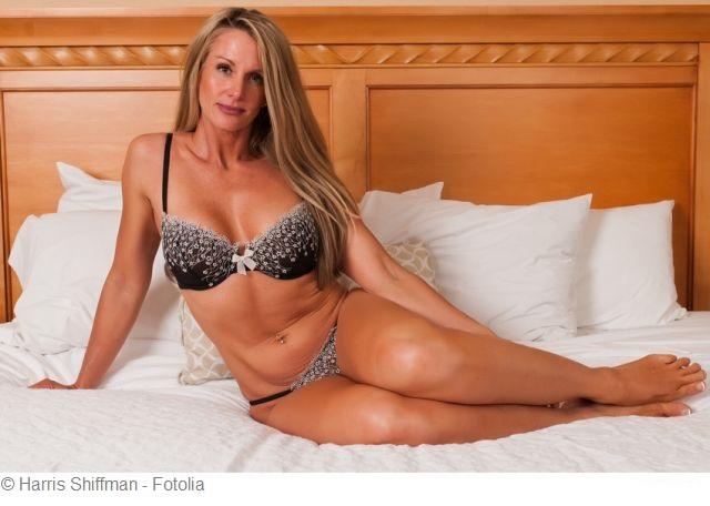 reife Blondine posiert auf Bett