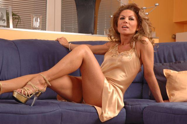 Sexy blonde Frau posiert auf der Couch