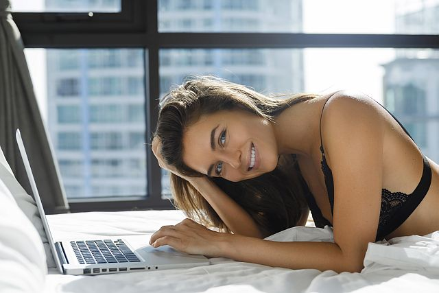 Sexy woman in black lingerie lying on the bed and using laptop