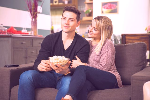 couple being romantic while watching films on the sofa