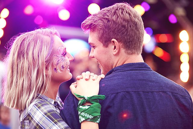 attractive blonde girl approaching a handsome guy at a festival