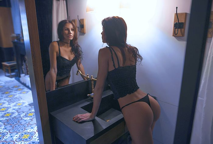 Attractive alpha lady in underwear, looking at herself in the mirror