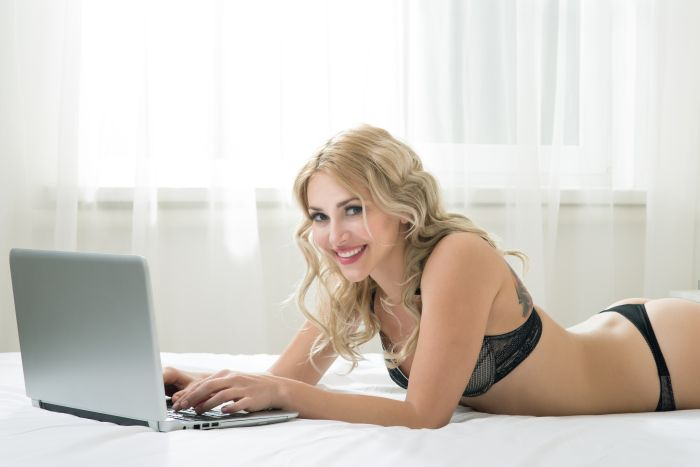 Woman in black lingerie chatting on her laptop