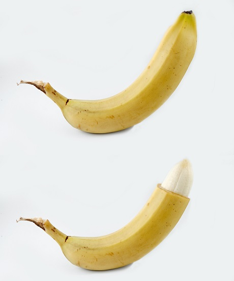 Two bananas, one with the top of its peel removed