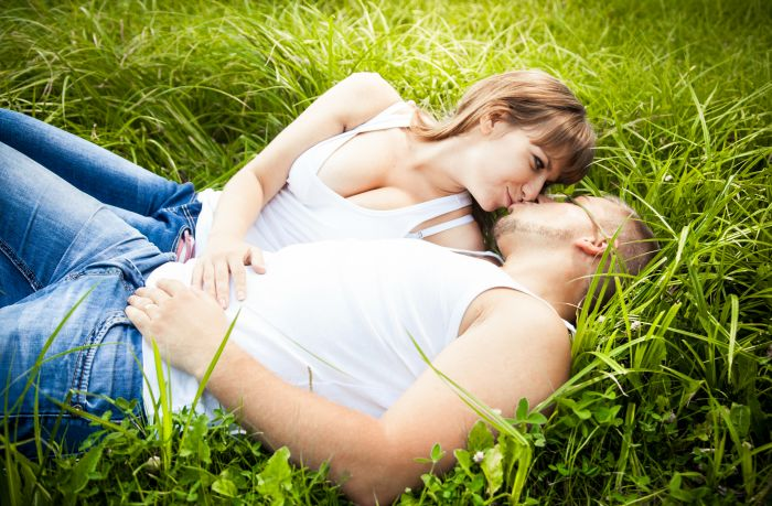 couple making out in a field of grass