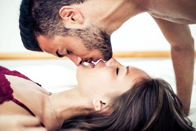 Man caressing blindfolded woman