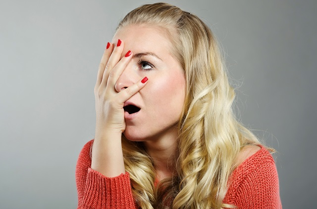 Annoyed woman performs a facepalm on herself